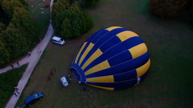 outspread sıcak hava balon zarf zeminde, şişirme insanlar uçuş hazırlanıyor - zeplin stok videoları ve detay görüntü çekimi