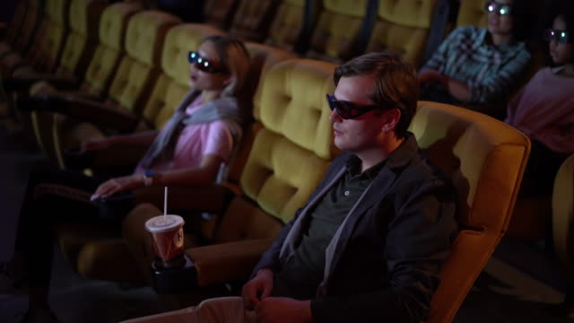People is sitting watching a 3D movie