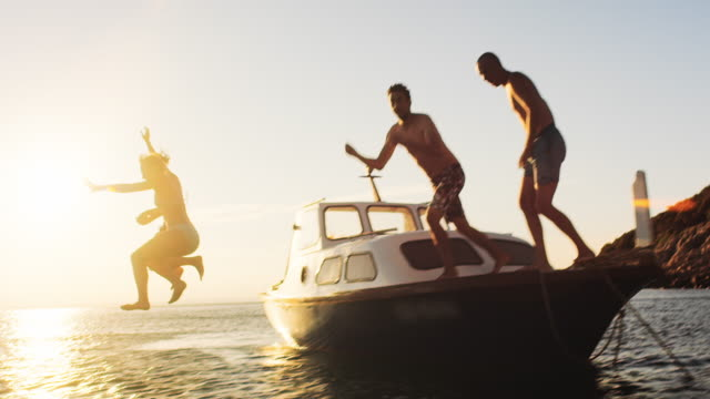 slo mo people jumping off the boat in sunset - tuffarsi video stock e b–roll
