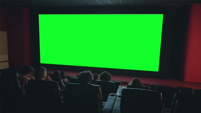 vidéos et rushes de les gens regardant le grand écran vert de clé de chrome dans le film appréciant le film - cinéma