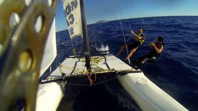 personer som flyttar över havet på vindsurfing katamaran, viftande på skeppet på horisonten - skrov bildbanksvideor och videomaterial från bakom kulisserna
