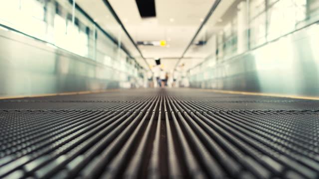 человек движется на плоской подошве эскалаторов в аэропорту - пешеходная дорожка путь сообщения стоковые видео и кадры b-roll