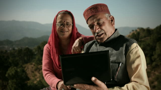 People of Himachal Pradesh: Senior couple using laptop computer People of Himachal Pradesh: Senior man using laptop computer and showing it to his wife. Both of them are in traditional clothing, the couple is giving toothy smile and enjoying entertaining features of laptop computer in sunny day, trees and mountains are in the background. indian culture stock videos & royalty-free footage