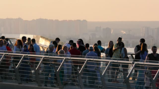 people on a foot bridge admire the city video