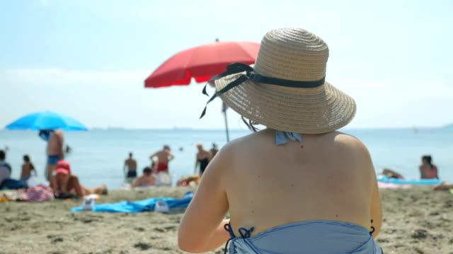 menschen am strand im heißen sommertag - sonnenbaden stock-videos und b-roll-filmmaterial