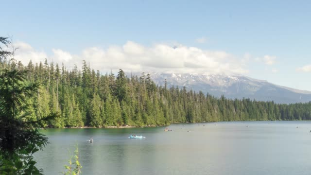 People on boats and kayaks having fun at Lost Lake in Oregon during a sunny day.