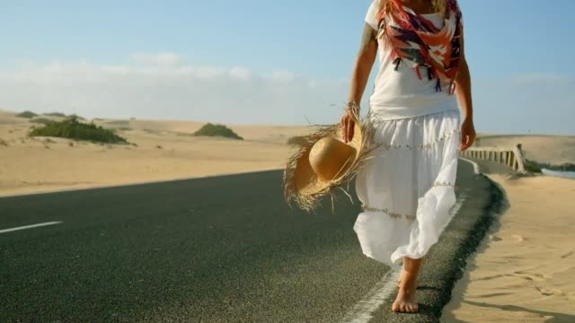 People on holiday summer vacation outdoor caucasian woman walking on the road with sand and desert on the sides - beach and outdoor leisure activity for beautiful tourist with clear dress and hand made hat - beautiful landscape in background
