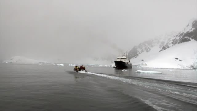 Mensen op rubberboot en schip in de oceaan van Antarctica. video