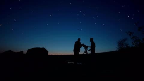 vidéos et rushes de personnes sur terre à la recherche par le biais de télescope - exploration