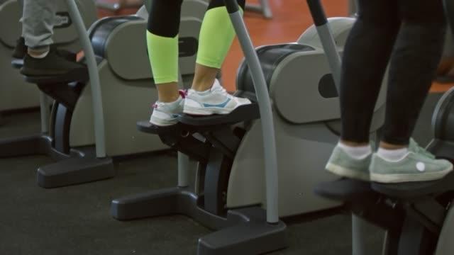 vídeos de stock e filmes b-roll de people on stepper machines in gym - aparelho de musculação