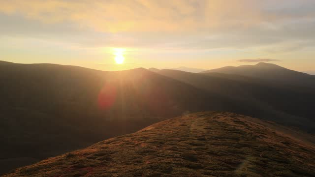 People on the mountain top meet the first rays of rising sun