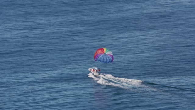 People parasailing off the coast of Waikiki, Hawaii. Oahu, Hawaii circa-2018.  People parasailing off the coast of Waikiki, Hawaii.  Shot with Cineflex and RED Epic-W Helium. oahu stock videos & royalty-free footage