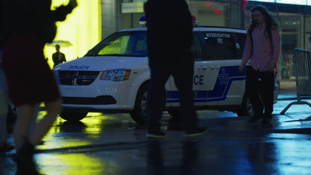 People passing by a police car People passing by a parked police car, in Montreal, Canada. stationary stock videos & royalty-free footage