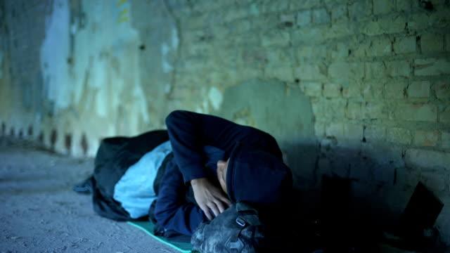 люди, проходящие мимо бедного бездомного молодого человека, равнодушного эгоистического общества, бедности - сбежавший из дома стоковые видео и кадры b-roll
