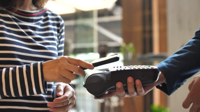 ショップで携帯電話で非接触支払いを支払う人々 - クレジット決済点の映像素材/bロール