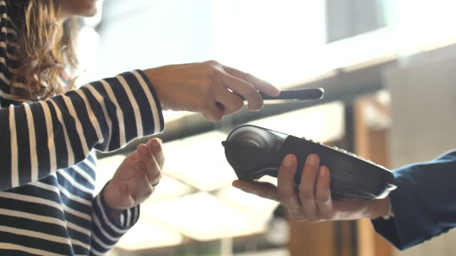 people paying contactless payment with mobile phone in a shop - contactless payment stock videos & royalty-free footage