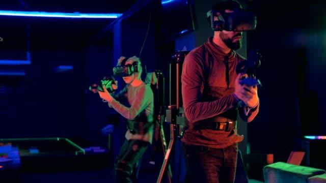 people playing virtual reality futuristic games - fianco a fianco video stock e b–roll