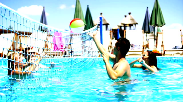 People playing vollebay in swimming pool and having beers. Group of young adults enjoying at local swimming pool. There are two guys and two girls. Playing volleball with beach ball. Static camera, horizontal shot. beach volleyball stock videos & royalty-free footage