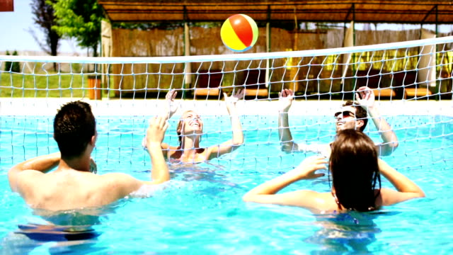 People playing volleybay in swimming pool and having beers. video