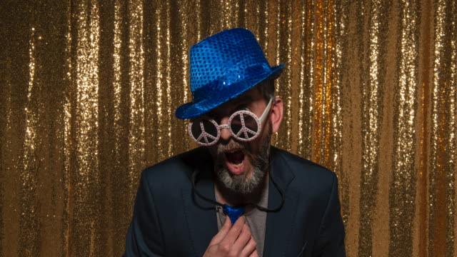 People posing in the photo booth wearing fun props