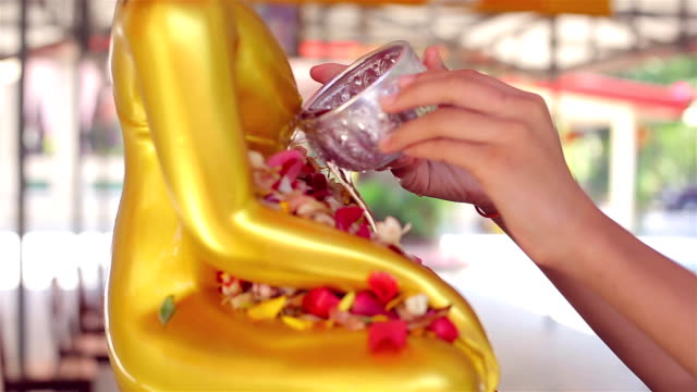 People pour water over Buddha statues at the Songkran Days or traditional Thai's New Year. It is a part of Buddhist rituals/traditions for Thais. video