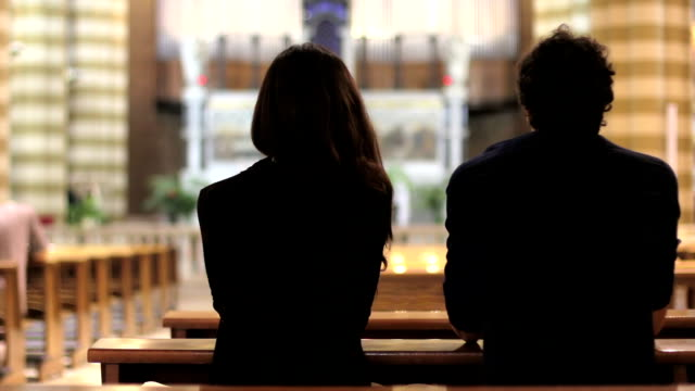 People pray in a church video