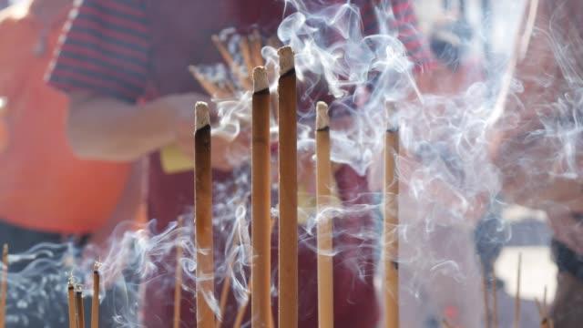 道教寺院の内部でお辞儀をし、旧正月のお祝いの間に線香を持つ人々。砂で満たされたお香の大きな屋外ポットは、テーブルの上にとどまっています。クローズ アップ。4k - 幸運点の映像素材/bロール