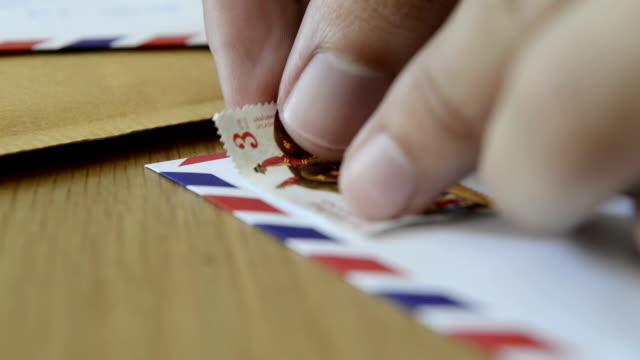 vídeos de stock e filmes b-roll de cngloth97-pessoas colocando marcas de letra e embalagem - correio