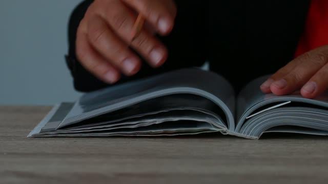personer som läser gamla boken för utbildning lärande koncept: young man öppna lärobok för läs slappna av eller studera söka information i böcker för kunskap. - stavning bildbanksvideor och videomaterial från bakom kulisserna
