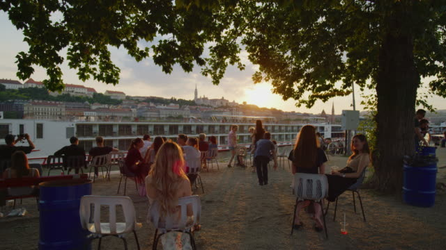 People relaxing at a riverside bar Evening view of people relaxing at a riverside bar next to the Danube, in Budapest. hungary stock videos & royalty-free footage