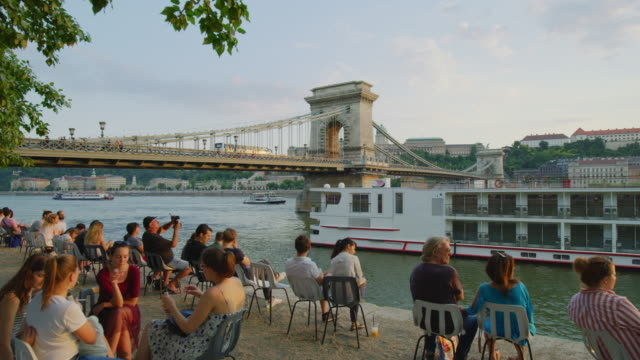 People relaxing on Danube river bank People relaxing on Danube river bank, near the Szechenyi Chain Bridge, in Budapest. hungary stock videos & royalty-free footage