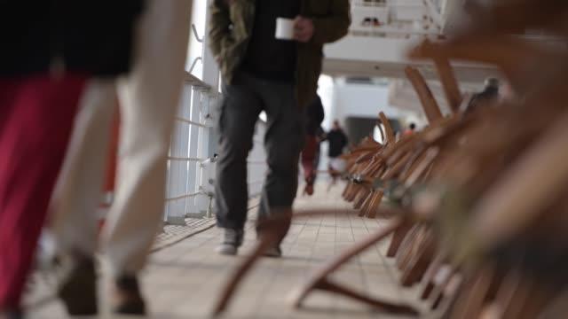 persone che si rilassano mentre camminano sul ponte principale della nave da crociera. - crociera video stock e b–roll