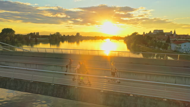 aerial people riding electric scooters on a bridge at sunset - monopattino elettrico video stock e b–roll