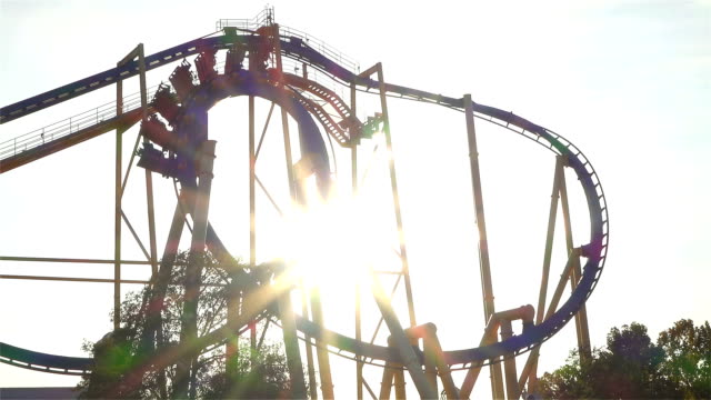 SLOW MOTION: People riding extreme roller coaster over the sun video