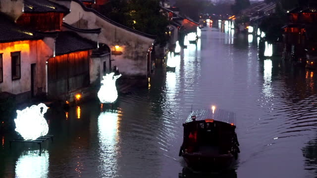 people rowing boat in river of traditional chinese water village. video