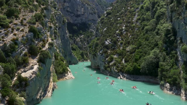 People sailing on pedal boats at the Verdon Gorge between Alps mountains in Provence, France. Waters of Verdon River have startling turquoise-green color. Aerial shot, UHD