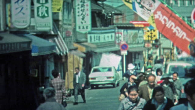 1972: People shopping at outdoor Japanese marketplaces and city streets.