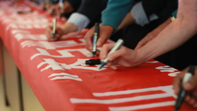 People Signing Chinese on a Red Banner video