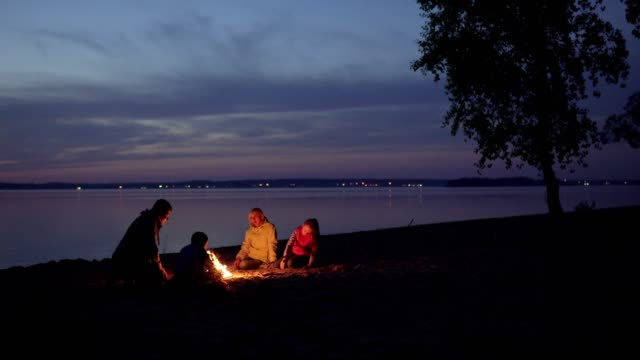 people sit by fire during family hike at night beach by sea - falò spiaggia video stock e b–roll