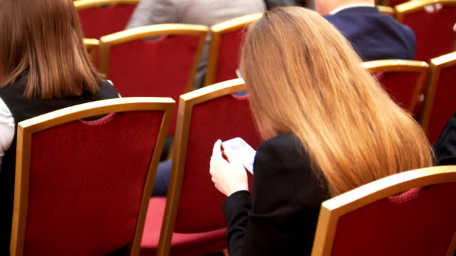 People sit in large hall on red chairs at business conference, women with smartphone in hands video
