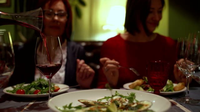 people sit in the restaurant. the waiter pours the wine from a decanter in glass - decanter video stock e b–roll