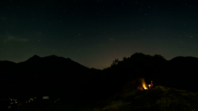 People sitting around campfire at starry moonlight night time lapse. video