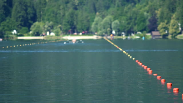 People sitting in boats and rowing, view on water sports competition, slow-mo