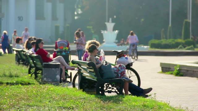 bankların üzerinde oturan insanlar içme suyu sıcak havalarda. sakin ol - cumhuriyet günü stok videoları ve detay görüntü çekimi