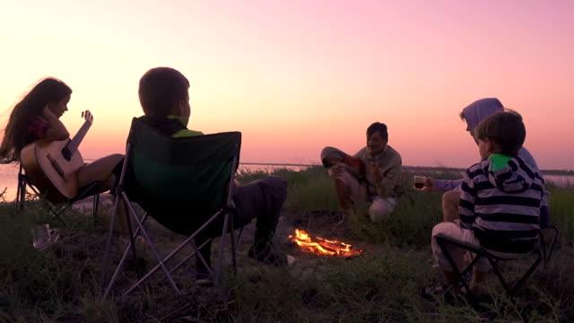 gün batımında kamp ateşi ile sahilde oturan insanlar - şenlik ateşi stok videoları ve detay görüntü çekimi