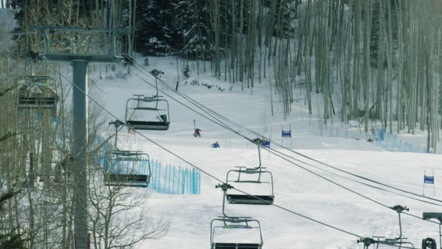 People Ski the Slopes in the Background while a Ski Lift Operates in the Foreground at a Colorado Mountain Ski Resort in Winter (Beaver Creek)