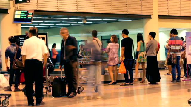 People stand queueing for load bag to back home video