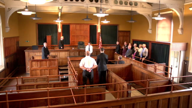 People stand up as Judge Enters Court (USA flag) Stock HD video clip footage of the people standing as a Judge walks into Court - Crane Shot - USA flag legal trial stock videos & royalty-free footage
