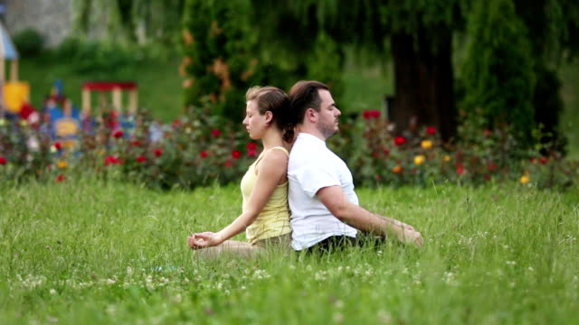 People stretching before doing exercises. Young yoga instructors practice in a city park on green grass. Successful caucasian man and woman taking a rest. People stretching before doing exercises. Young yoga instructors practice in a city park on green grass. Successful caucasian man and woman taking a rest. Close up shot. mental wellbeing stock videos & royalty-free footage