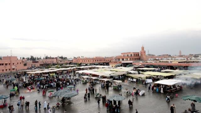 gente passeggiare intorno cabine e bancarelle di jemma dar fna, marrakech, marocco - souk video stock e b–roll